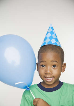 African boy wearing party hat and holding balloon Stock Photo - 16092729