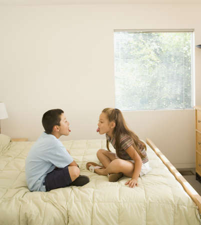bedclothes: Asian brother and sister sticking tongues out
