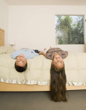 Asian brother and sister laying with heads off bed Stock Photo - 16092739