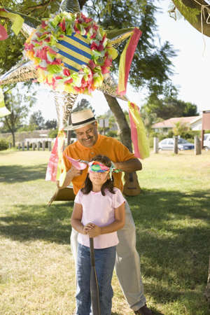 pinata: Hispanic girl being blindfolded next to pinata outdoors