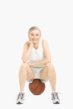 exerting: Senior Hispanic woman sitting on basketball LANG_EVOIMAGES