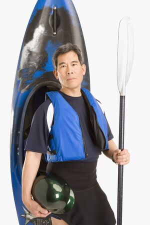 jeopardizing: Senior Asian man standing next to kayak