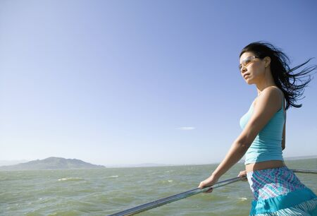 jeopardizing: Asian woman leaning on rail of boat LANG_EVOIMAGES