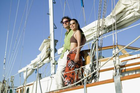jeopardizing: Low angle view of couple on sailboat LANG_EVOIMAGES