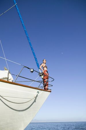 Asian woman standing on bow of sailboat Stock Photo