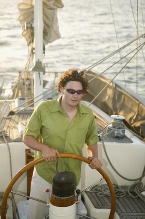 ハイアングルビュー: 男のヨットをステアリングのハイアングル LANG_EVOIMAGES