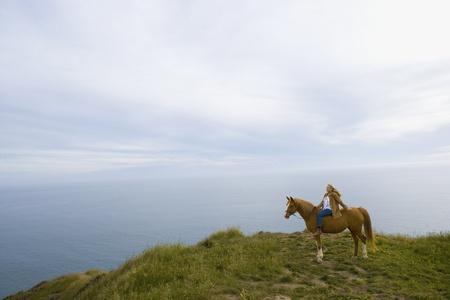 50: Senior woman horse riding bareback on cliff