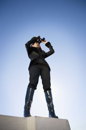 Low angle view of woman looking through binoculars