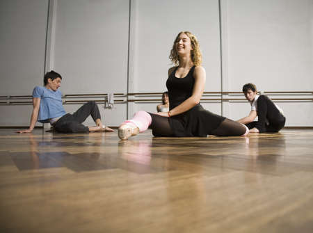 3 4 length: Hispanic dancers stretching in dance studio LANG_EVOIMAGES