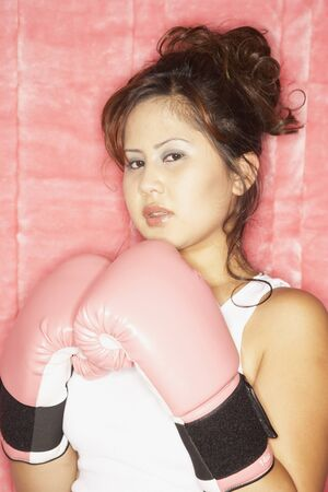 exerting: Portrait of Asian woman wearing boxing gloves