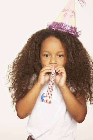 relishing: African girl wearing party hat and blowing noise maker