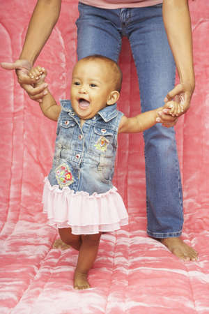 mother helping baby: Mother helping baby daughter walk LANG_EVOIMAGES