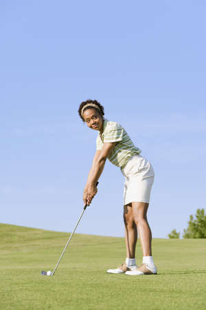 one mid adult woman only: African woman playing golf