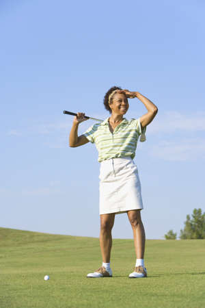one mid adult woman only: Portrait of African woman on golf course LANG_EVOIMAGES