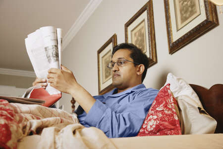bedcover: Indian man reading newspaper in bed