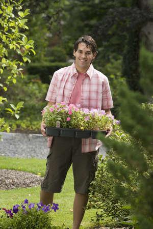 seeding: Hispanic man holding flat of flowers