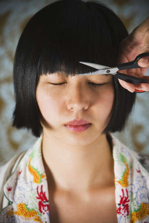 exactitude: Asian woman having bangs trimmed LANG_EVOIMAGES