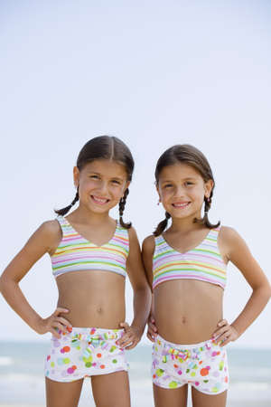 fond of children: Hispanic sisters wearing matching bathing suits LANG_EVOIMAGES