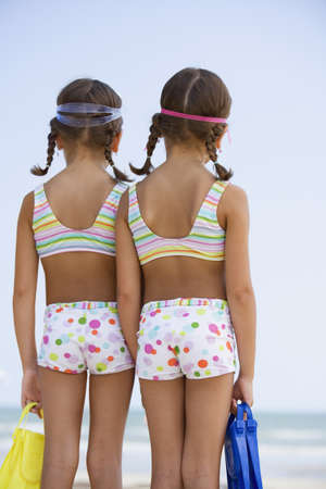 two persons only: Hispanic sisters wearing matching bathing suits LANG_EVOIMAGES
