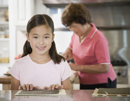 gramma: Portrait of Asian girl in kitchen with grandmother