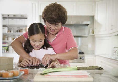 Asian grandmother and granddaughter making sushi roll Stock Photo