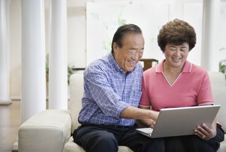 couple on couch: Senior Asian couple looking at laptop LANG_EVOIMAGES