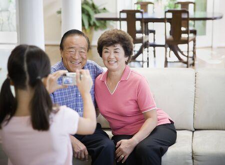 Asian girl taking photograph of grandparents
