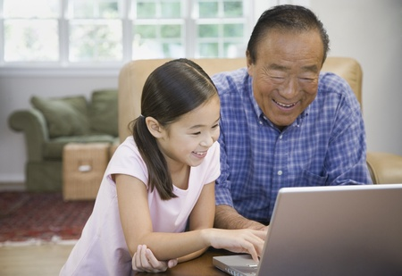 family: Asian grandfather and granddaughter looking at laptop