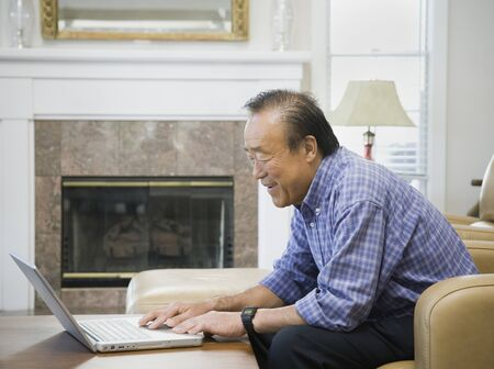 Senior Asian man looking at laptop