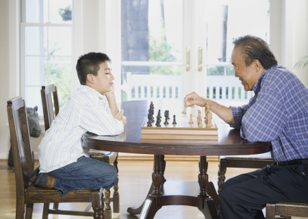 generation gap: Asian grandfather and grandson playing chess