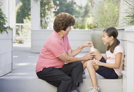 Asian grandmother bandaging granddaughters knee
