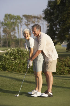 ninetys: Senior man helping wife with golf swing