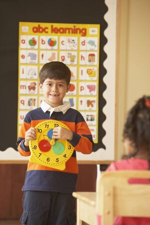 Young Hispanic boy holding up clock in class
