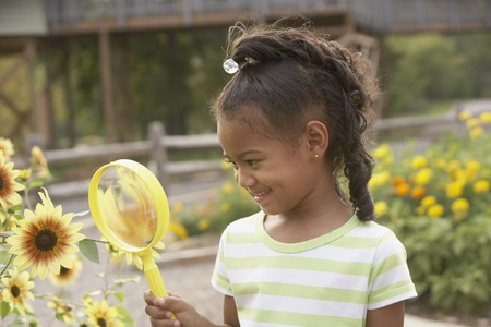 African girl looking at flower through magnifying glass Stock Photo - 16092901