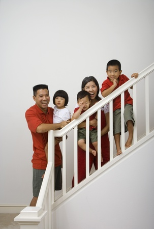Portrait of Asian family on stairs Banco de Imagens