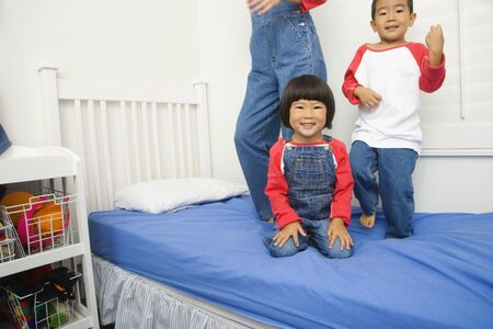 Asian siblings playing on bed Banco de Imagens