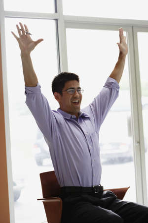 motioning: Asian businessman cheering in office
