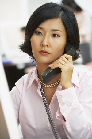 telephone: Asian businesswoman talking on telephone