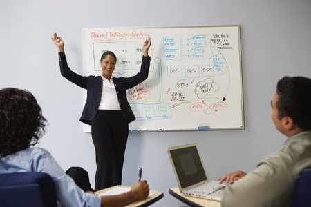 African businesswoman cheering in front of whiteboard