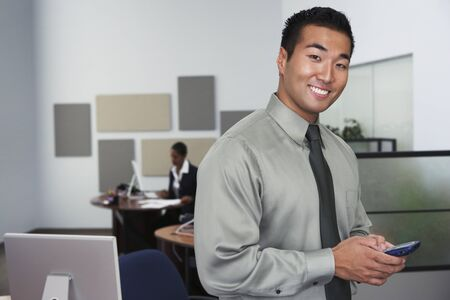 Portrait of Asian businessman holding cell phone Stock Photo - 16092941