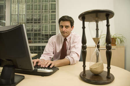 Hispanic businessman looking at hourglass on desk Stock Photo - 16092955