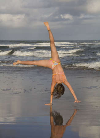 Woman doing cartwheel on beach Stock Photo - 16092956