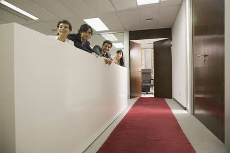 mischievious: Hispanic businesspeople looking over cubicle wall LANG_EVOIMAGES