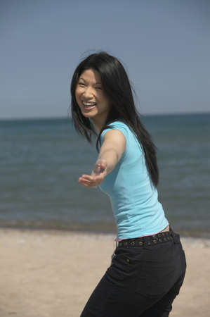 Asian woman laughing with outstretched hand at beach Stock Photo - 16092974