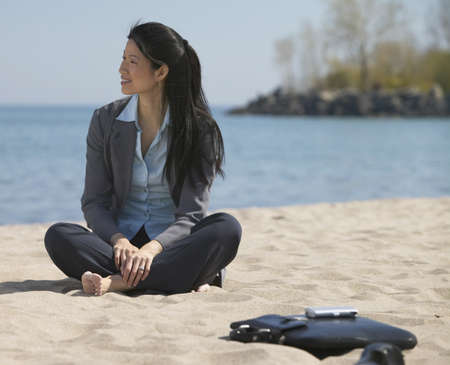 finding a mate: Asian businesswoman sitting at beach with bare feet LANG_EVOIMAGES