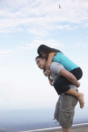 Asian man giving girlfriend piggy back ride at beach Stock Photo - 16092977