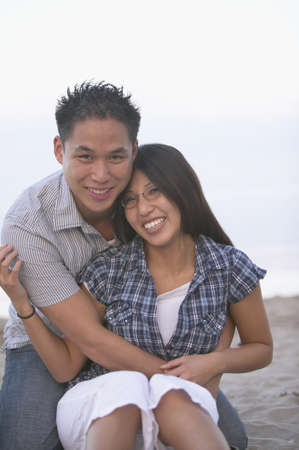 stepping: Asian couple hugging and smiling at beach