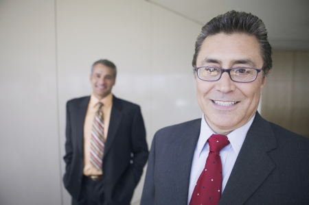 Portrait of Hispanic businessman with coworker in background Stock Photo