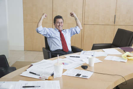 prevailing: Hispanic businessman cheering at conference table