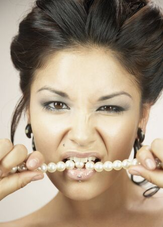 Woman with hair up biting pearl necklace Stock Photo - 16093027